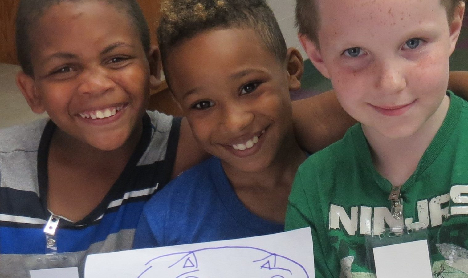 smiling children holding a drawing